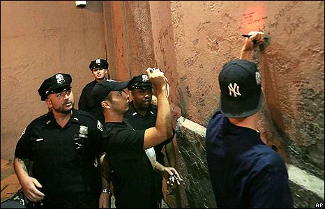 Police officers approach a Yankee baseball fan as he writes on the wall of the Yankee Stadium in New York