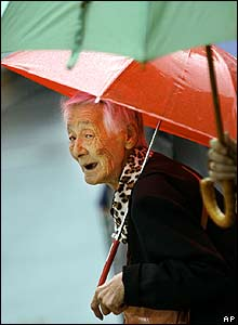 An elderly woman waits at a crossing in the rain in Tokyo, Japan