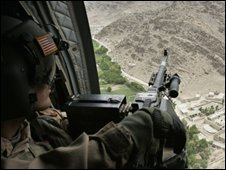 A US machine gunner looks out of a helicopter as troops and materials are transported in Nangalam, eastern Afghanistan, Monday, Sept. 4, 2006.