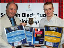 Alan elliot receives his black pudding award from  Jim Fox