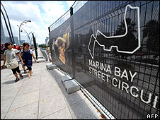 Tourists walk past an advert for the Singapore Grand Prix
