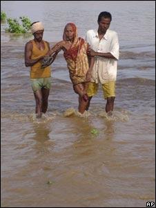 Villagers help an elderly woman cross floodwaters in Orissa on Sept 20, 2008.