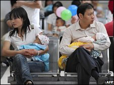 A mother and a father hold their babies as they wait for treatment in a children's hospital in Beijing on September 23, 2008