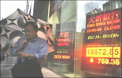 Man walks past panel displaying the closing Hang Seng Index outside a bank in Hong Kong, 23 September 2008