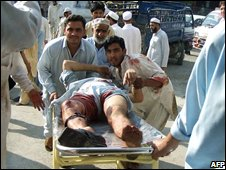 Pakistani people carry a protestor, injured by firing police, on a stretcher outside a hospital in Mingora, the main city in Swat on September 23, 2008.