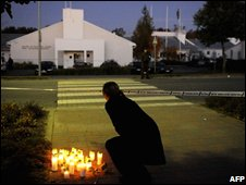 A woman lays a candle at the Seinajoki vocational centre