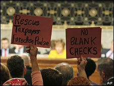 Protesters hold up signs as lawmakers quiz administration officials on Capitol Hill on 23 September 2008