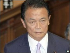Taro Aso stands up among fellow lawmakers applauding after he won the vote to become prime minister