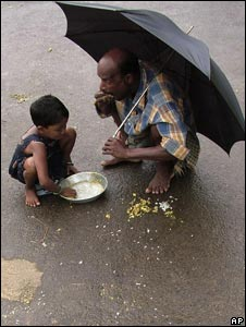 A flood affected villager shares food with his daughter in Kendrapada district in Orissa on 23 September 2008