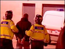 An arrested fan is led away