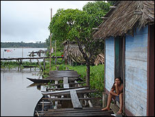 A woman sits outside a house on the banks of the River Orinoco