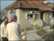 Elan Ben-Shlomo (L) and an unidentified woman outside a gutted house in Yitzhar