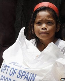 A displaced Filipino girl receives a sack of rice from World Food Programme, 17 Sept