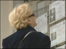 A woman looks at a real estate ads in Paris