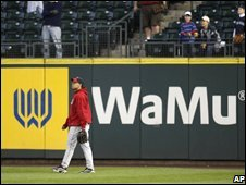 A baseball player walks past a WaMu advert in Seattle