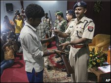 A United Liberation Front of Assam militant hands over his weapon to police