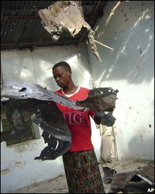 A man collects debris after his house was hit by a mortar, 26 September 2008