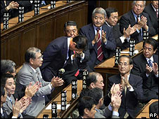 Taro Aso bows among fellow lawmakers applauding after he won the election to succeed Yasyo Fukuda as Japan's prime minister