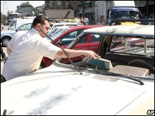 A man cleans broken glass from his car in Damascus, Syria (27/09/2008)