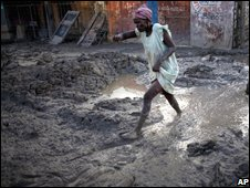 Woman walks through mud in Gonaives, which was badly damaged by the storms 