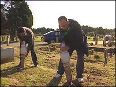 Volunteers fixing desecrated headstones