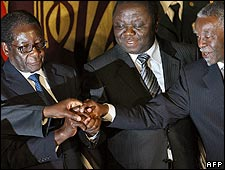 L-R: Robert Mugabe, Morgan Tsvangirai and Thabo Mbeki hold hands