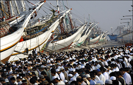 Indonesian sailors and their families pray in front of their ships in Jakarta's port at the start of the festival of Eid al-Fitr