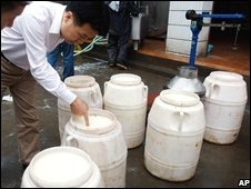 Chinese food safety officials check milk at a collection station in Chengdu, Sichuan province