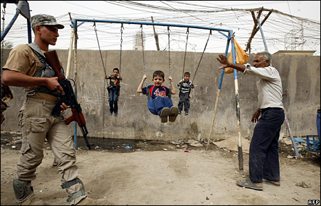 An armed member of a Sunni Arab Awakening Council walks past children using swings in the centre of Baghdad