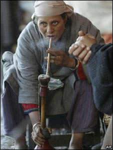 A woman smokes a hookah in India