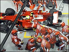 Felipe Massa pulls away from the Ferrari pit with his fuel hose still attached during the Singapore Grand Prix