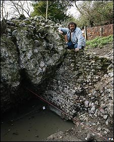 Tony Wilmott next to the fallen Roman wall and above the medieval dock