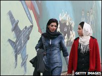 Iranian women walk past anti-US mural