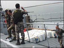 Men near drums full of cocaine on ship