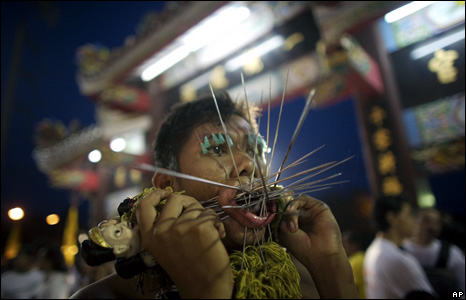 A devotee of the Ban Tha Rue Shrine pierces himself with spikes prior to a procession during the Vegetarian Festival in Phuket, Thailand