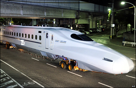 The front section of a new Shinkansen, or bullet train, is transported through the streets of Fukuoka in southern Japan.