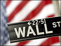 Wall Street sign in front of the American flag hanging on the New York Stock Exchange