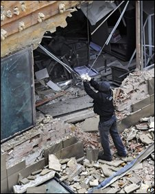 Firefighters remove rubble from the building
