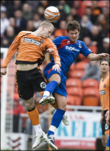 Dundee United's Scott Robertson jumps with Caley Thistle's Andy