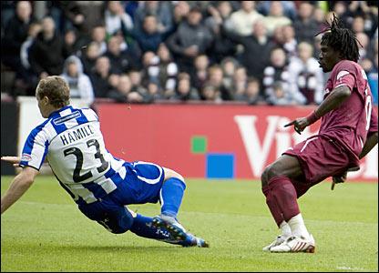 Hearts midfielder Laryea Kingston strikes the ball into the net as Kilmarnock defender Jamie Hammil (23)  looks on