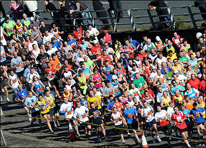 Hundreds of runners stream along the course
