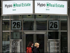 People walking past a branch of Hypo Real Estate in Berlin