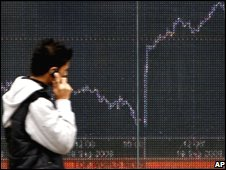 A man passing a screen with the FTSE financial index