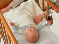 Baby lying in a cot