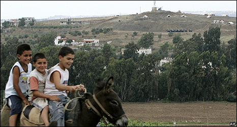 Lebanese children ride a donkey near the border with Syria, where Syrian forces are visible in the background