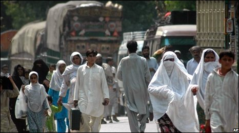 Pakistani people walk along the main road that leads to the troubled area of the Swat valley in northern Pakistan Wednesday, July 30, 2008