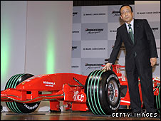 Bridgestone president Shoshi Arakawa poses with a Ferrari fitted with the green-grooved tyres that will be used at the Japanese Grand Prix