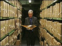 Man in a library of document folders