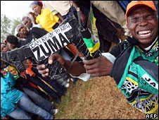 "A Jacob Zuma supporter holding a fake machine gun with ""I am ready to kill 4 Zuma"" on it"