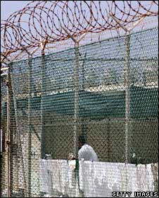 Inmate behind fence at Guantanamo Bay